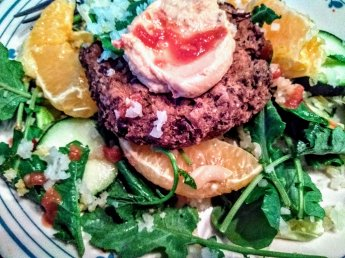 Hummus Topped Veggie Burger On Greens With Citrus