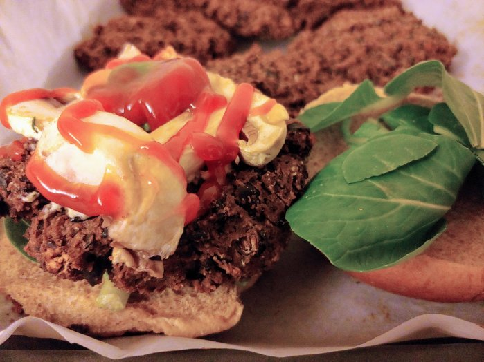 My ultimate black bean burger here is topped with fresh mushrooms, red sauce, and a schmeer of some additional Miyoko's garlic and herb cashew cheese. Fresh spinach below the burger and on the top bun.
